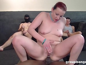 Gangbang on the floor with a lot for guys and a redhead babe